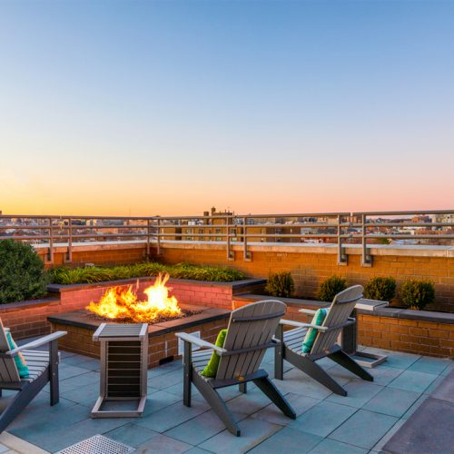photo of rooftop fire pit surrounded by chairs at Jefferson MarketPlace apartments taken at dusk
