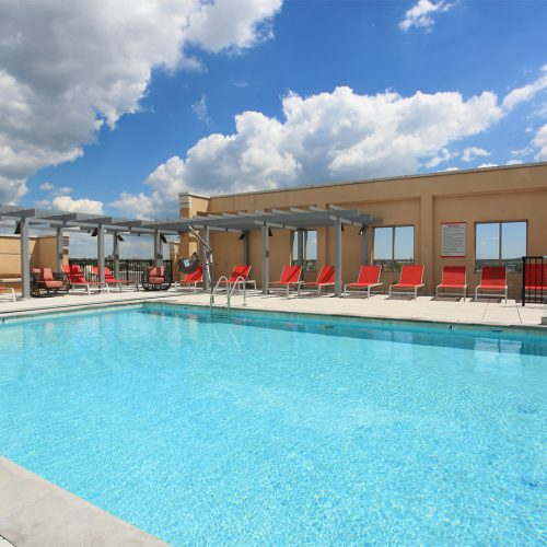daytime photo of the rooftop pool and sundeck at Jefferson MarketPlace apartments with a blue sky filled with fluffy clouds and red lounge chairs surrounding the pool