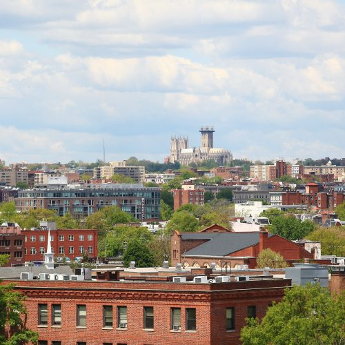 photo of the view of Northwest Washington DC as seen from the roof of Jefferson MarketPlace apartments with a blue cloud-filled sky and rooftops and trees in the distance