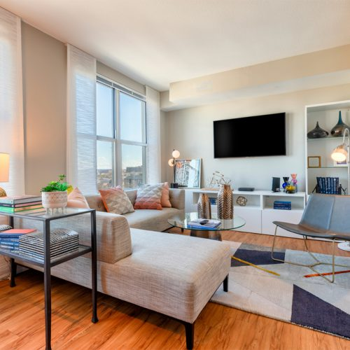 Image of a living room at Jefferson MarketPlace apartments in Washington, DC with large gray sectional couch, two glass tables, modern chair, area rug, large painting on one wall and a flat screen TV on the other and a view of DC out the window